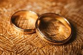 Intersecting Pair Male And Female Wedding Gold Rings Lie On Background Covered With Strokes Of Oil B poster