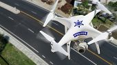 Police Unmanned Aircraft System, (UAS) Drone Flying Above A City Street. poster