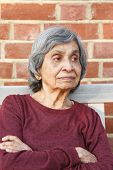 Elderly Asian Indian Woman Sitting Alone. Healthy And Slim Appearance, May Also Depict Loneliness Or poster