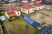 Aerial Top View Of Residential Area With New Houses With Roof Solar Photo Voltaic Panels, Wind Turbi poster