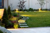 Backyard Of The Mansion With A Flowerbed And A Lawn Of Green Grass With A Marble Walkway Of Square T poster