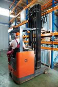 Warehouse worker distributing goods in a storehouse with forklift truck loader stacker