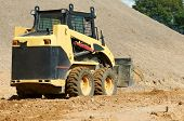 stock photo of skid-steer  - skid steer loader moving sand soil at construction area outdoors - JPG