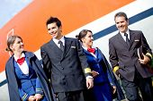 Group of pilots and flight attendants geting off an airplane