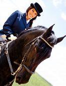 Elegant woman horseback riding outdoors and smiling