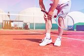 Low section of mature man holding tennis racket while suffering from knee pain on red tennis court d poster