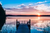 Idyllic View Of The Long Pier With Wooden Bench On The Lake. Sunset Or Sunrise Over The Water. poster