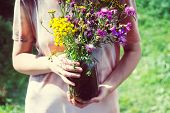 A Bouquet Of Wildflowers In The Hands Of A Young Girl In A Light Light Summer Dress Against A Backgr poster