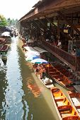 Bangkok August 2012.Wooden flat boats busy ferrying people at Damoen Saduak floating market. A tradi
