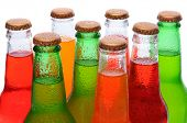 Closeup of several assorted flavors of soda pop. Orange, lemon lime, and strawberry soda bottles necks only over a white background.