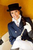 Elegant female jockey wearing a hat in a carriage