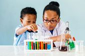 Two Curious African American Children Conducting Interesting Chemistry Experiments With Colorful Liq poster
