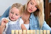 foto of babysitter  - Young girl playing with dominoes - JPG