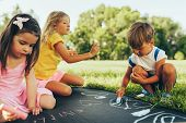 Outdoors Image Of Kids Sitting On The Green Grass Playing With Colorful Chalks. Happy Children Drawi poster