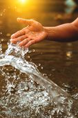 Hand Fetch Water And Have Water Splash With Sunset. poster