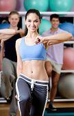 Sexy weibliche Trainer funktioniert mit ihrer Gruppe in der Turnhalle in einer Fitness-Klasse um Fit zu bleiben