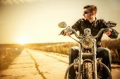 stock photo of biker  - Biker man sits on a bike - JPG