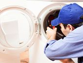 stock photo of pipefitter  - Technician repairing a washing machine - JPG