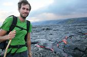 Hawaii hiker hiking by flowing lava from Kilauea volcano around Hawaii volcanoes national park, USA.
