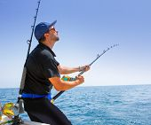 stock photo of offshoring  - blue sea offshore fishing boat with fisherman holding rod in action - JPG