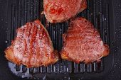 fresh grilled bloody beef steaks on black grill plate isolated on white background
