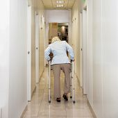 stock photo of zimmer frame  - Rear view of woman with Zimmer frame walking in hospital corridor - JPG
