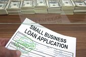 stock photo of borrower  - Approved small business loan application and dollar bills - JPG