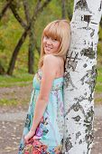 stock photo of barrel racing  - young beautiful woman in a park near a birch - JPG