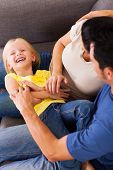 stock photo of tickle  - parents tickling little daughter on sofa - JPG