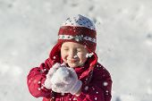 stock photo of snow-slide  - Little girl is playing outside in cold winter - JPG