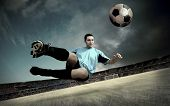 Постер, плакат: футболист на футбольном поле стадиона с драматическим небо