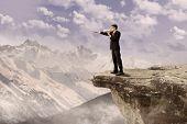 Businessman Using Speaker On Cliff