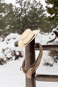 A cowboy's wrangler hat and lasso hanging on a corral fence post in a snowy, mountain ranch.