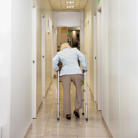 image of zimmer frame  - Rear view of woman with Zimmer frame walking in hospital corridor - JPG