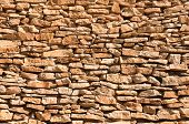 Old Wall Made Of Big And Little Yellow Stones