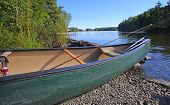 image of moosehead  - Beached green hull canoe with fly fishing tackle inside - JPG