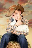Farm Boy Sitting On Bale Of Hay Holding A Chicken