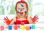 stock photo of finger-painting  - little girl painting with paintbrush and colorful paints - JPG