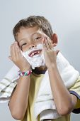 Smiling child is placed shaving cream on his face