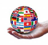 picture of flags world  - Travel services and international business concept with a globe and international flags of the world on a man hand - JPG