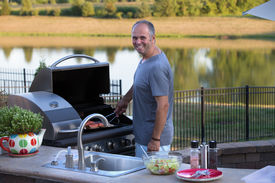 stock photo of braai  - Middle age man cooking salmons at the outside kitchen barbecue - JPG