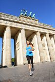 Berlin lifestyle. Running woman in Berlin, Germany by Brandenburg Gate jogging living healthy lifestyle. Female runner jogging. Urban fitness girl working out outdoors in jacket.