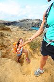 Help - hiker woman getting helping hand hiking on hike smiling happy. Tourist backpackers walking on