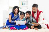 Indian Asian family using tablet pc computer online shopping with credit card at home. India family living lifestyle. Happy smiling parents and children.