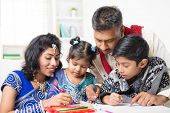 Asian Indian family drawing and painting picture at home. India family lifestyle. Happy parents and