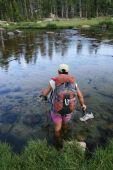 Frau Backpacker über Fluss waten