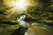 Sun rays shining over a mountain river with big cliffs and rocks