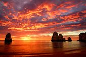 stock photo of sunrise  - Stunning sunrise over the ocean with beautiful red clouds and a few cliffs standing out of the water - JPG
