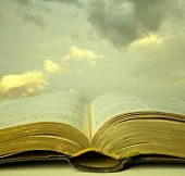 stock photo of mystical  - Detail of an old holy bible open with a beautiful and mystical sky in the background in a golden light - JPG