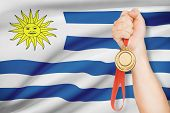 Medal In Hand With Flag On Background - Oriental Republic Of Uruguay